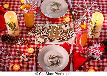 Sweet Christmas decorated table with candles, cookies,...