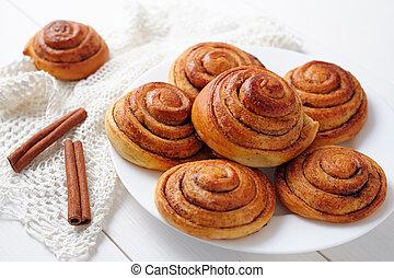 Sweet cinnamon bun rolls christmas delicious dessert on white vintage table. Traditional swedish kanelbullar baked pastry.