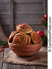 Sweet cinnamon bun rolls or kanelbullar christmas homemade norwegian delicious sweet dessert with spice on vintage woonde table. Traditional swedish baked pastry