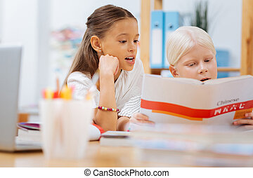 Sweet clever children spending time on studying
