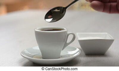 sweet coffee - pouring sugar into coffee cup on table.