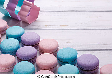 Sweet colorful macaroons on white wooden background. Space for text