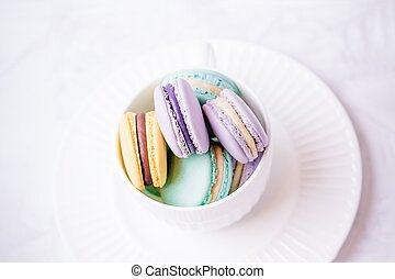 Sweet colourful french macaroons or macaron on white marble background. Top view, copy space
