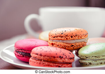 sweet colourful macarons dessert in the white plate with retro vintage filter