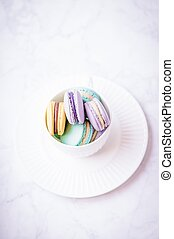 Sweet colourful pastel french macaroons or macaron on white marble background. Top view, copy space