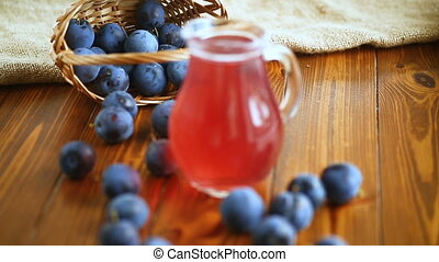 sweet compote of autumn blue plums in a glass decanter on a...