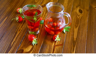 Sweet compote of ripe red strawberries in a glass decanter...