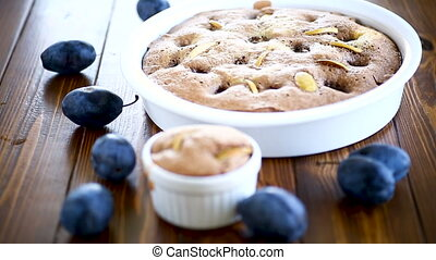 sweet cooked sponge cake with plums, on a table. - sweet...