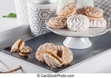 Sweet cookies on white tray with cups of coffee