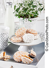 Sweet cookies on white tray with cups of coffee with green and white flower