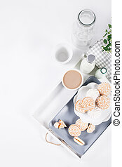 Sweet cookies on white tray with cups of coffee with green and white flower, top view