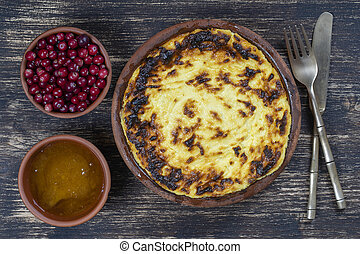 Sweet cottage cheese casserole with raisins and semolina on wooden table. Ceramic bowl with baked cottage cheese casserole , closeup, top view