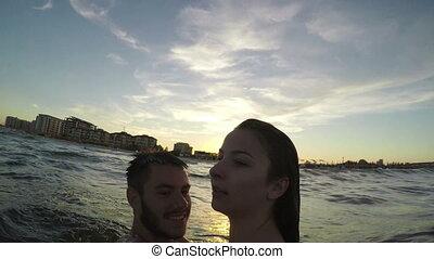 Sweet couple hugging and having fun in the sea