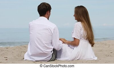Sweet couple in white clothes relax on the beach on a sunny ...