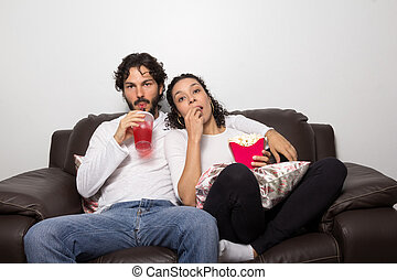 Sweet couple is at home watching movie. Romantic. Together and happy.