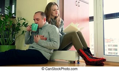 sweet couple relaxing on warm radiator at home. - sweet...