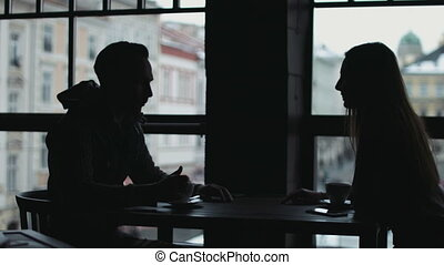 Sweet couple silhouette sitting at the cafe opposite to huge windows, chatting and holding each other hands.