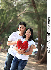 sweet couples dating - attractive young man embracing his...