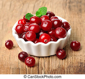 Sweet cranberries close up on wooden tables