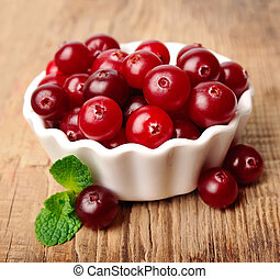 Sweet cranberries with leafs close up on wooden texture