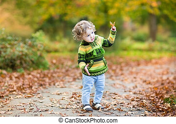 Sweet curly baby girl dancing in a colorful autumn park