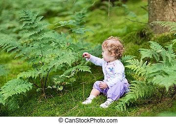 Sweet curly baby girl gathering wild raspberries in a beautiful