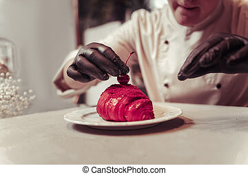Close up of a cherry being put on the croissant