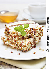 Sweet dessert. Two slices of cake on white plate with cup of...