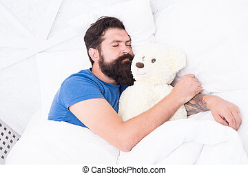 Sweet dreams. Bearded hipster play toy. Valentines day gift. Man sleep hug soft toy relaxing in bed. Cute teddy bear toy. Softness tenderness. Playful adult fall asleep. Good night. Sleep well