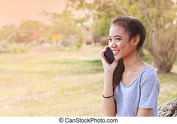 Asian woman sitting on stone using a mobile telephone