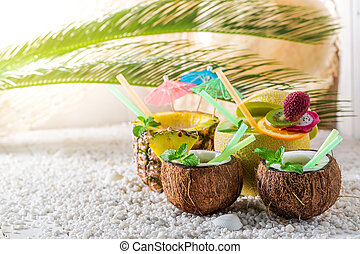 Sweet drinks in fresh fruits on sandy beach