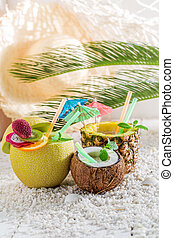 Sweet drinks in fresh fruits with cocktail umbrellas