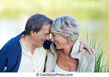 Sweet elderly couple in love sitting near the lake - An...