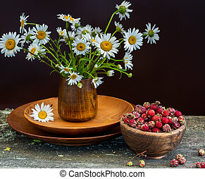 Sweet forest strawberries and a bouquet of daisies on a wooden background