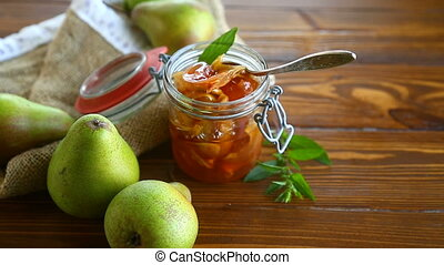 sweet fruit jam with apples and pears in a glass jar on a...