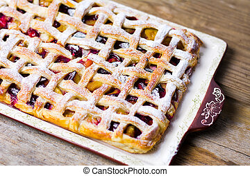 Sweet fruit pie with sugar on a tray