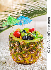 Sweet fruits salad in pineapple with cocktail umbrellas