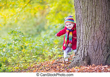 Sweet funny baby girl in a red coat and colorful hat and knitted
