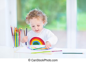 Sweet funny toddler girl painting a rainbow in a white room with