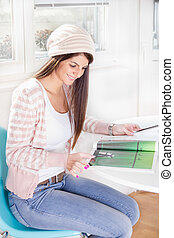 sweet girl by the window with magazine