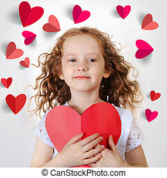Sweet girl holding red paper heart.