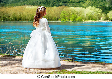 Sweet girl in communion dress outdoors.