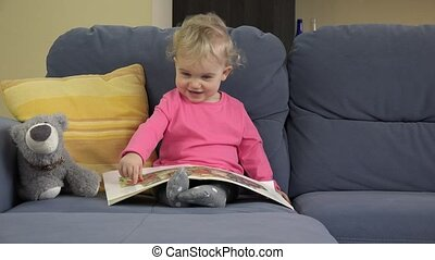 sweet girl read book on sofa in room. Education, childhood....