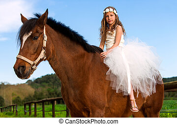 Close up portrait of cute girl with flower head band on horse back outdoors.
