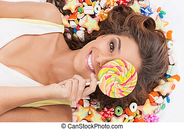 Sweet girl. Top view of beautiful young women holding a lollipop in front of her eye while lying on the floor covered with candies