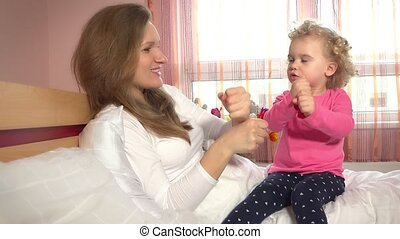 Sweet girls woman and child playing game with hands sitting on white bed