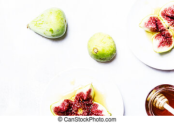 Sweet green figs with honey, gray background, top view