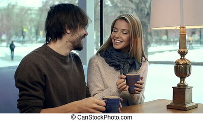 Sweet Hearts - Young couple drinking tea in cafe and...