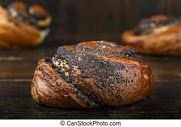 Sweet homemade bun with poppy seeds on a wooden background