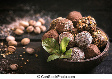Variety of sweet homemade chocolate pralines on wooden background, selective focus